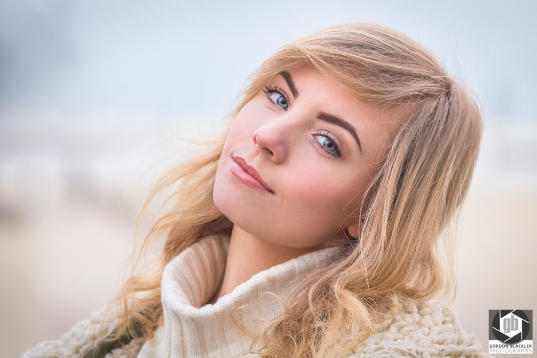 beautiful young blonde woman wearing a chunky white sweater