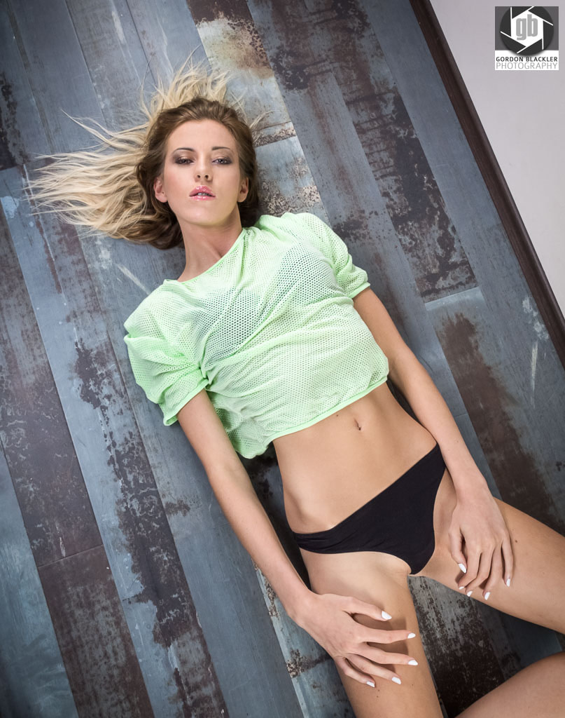 fashion portrait of a blonde woman lying on the floor wearing a green top and black sports briefs