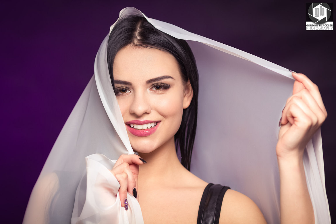 studio portrait of beautiful brunette who holds a white veil over her head