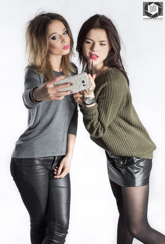 studio fashion portrait of two brunettes pulling funny faces while taking a selfie